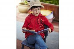 A child from Tigger's Honeypot reads outside